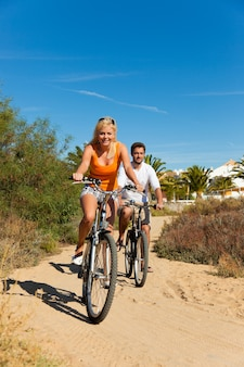 Couple in holidays cycling on beach