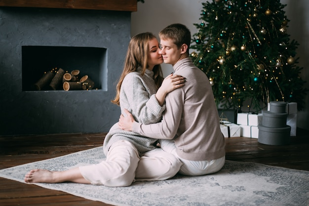 Couple at home at christmas time near beautifully decorated christmas tree