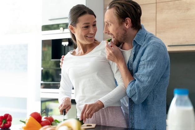 Coppia a casa che cucina insieme