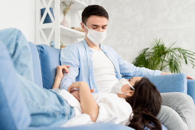 Couple at home on couch with medical masks