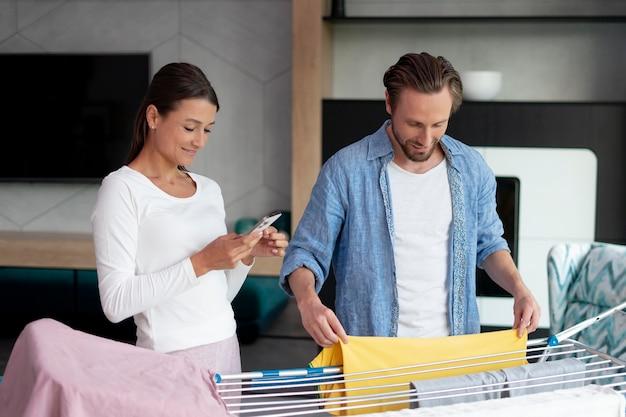 Coppia a casa che fa le faccende domestiche