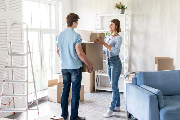 Couple at home preparing boxes to move out