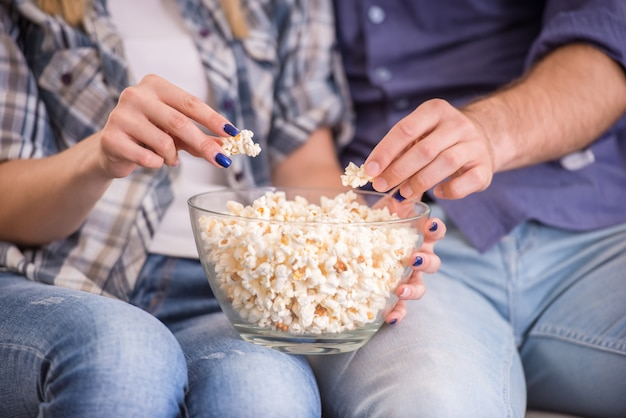 Couple at home sitting on couch, watch tv and eat popcorn.