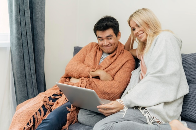 Couple at home together using laptop on the couch