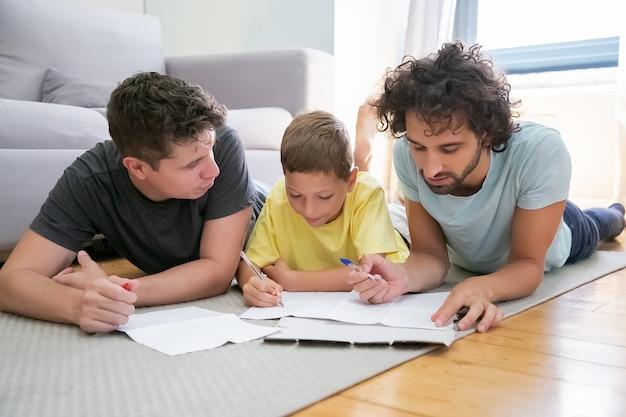 Coppia di genitori omosessuali che aiutano il ragazzo concentrato con il compito di scuola a casa, sdraiato sul pavimento a casa, scrivendo o disegnando su fogli. famiglia e concetto di genitori gay