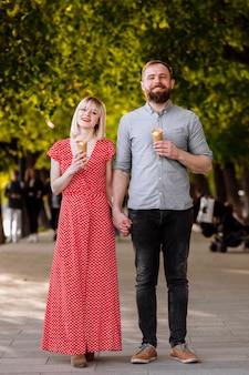 カップルを抱き締めると路上でアイスクリームを食べる。屋外でアイスクリームを共有し、笑顔の観光客のカップル。アイスクリームを食べている素敵なカップルの写真。