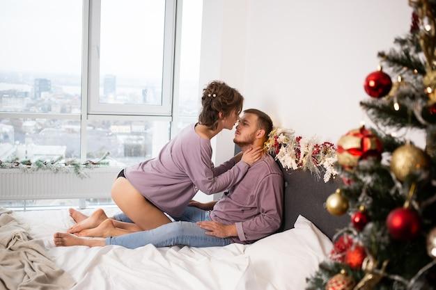 クリスマスの時期にお互いに家で抱き合ったりキスしたりするカップル