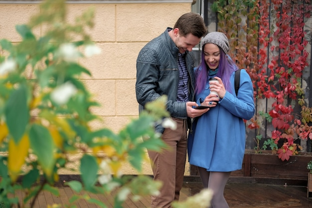 Пара обнимается и использует смартфон на улице