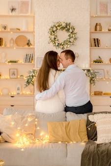 크리스마스 훈장에 집에서 포옹하는 커플