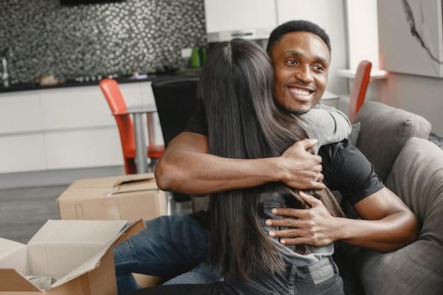 段ボール箱でいっぱいの新しいアパートで抱き合うカップル、引っ越し。新しいアパートに引っ越します。