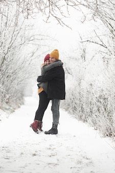 Couple hugging each other outdoors in winter