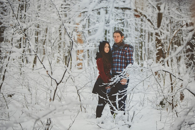 Couple hugging each other in winter forest