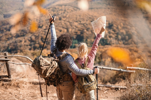 Couple hugging and holding hands up while standing on the glade and looking at view. woman holding map, on backs backpacks. backs turned. hiking concept.