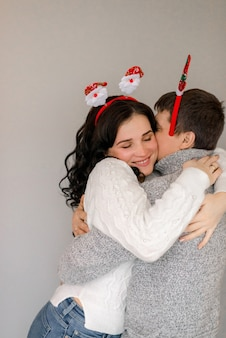 Couple hugging at home  in christmas accessories