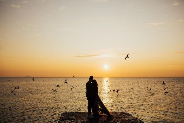海に沈む夕日の前で抱き締めるカップル。恋人たちと夕日を眺める。
