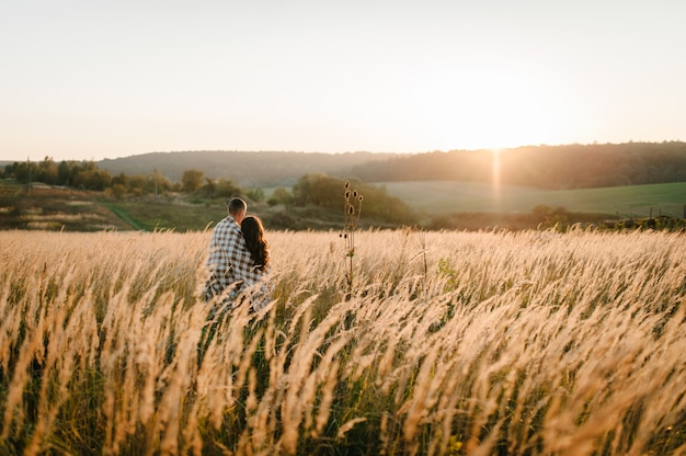 Couple hugging, people covered with blanket, at sunset in autumn an outdoor. at field grass.  full length standing back. close up.