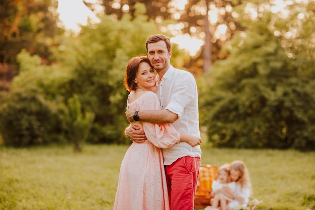 Couple hugging and posing at family picnic. kid's, focus is at mom and dad. copy space.