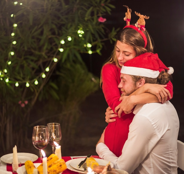 Couple hugging in santa hats at christmas dinner
