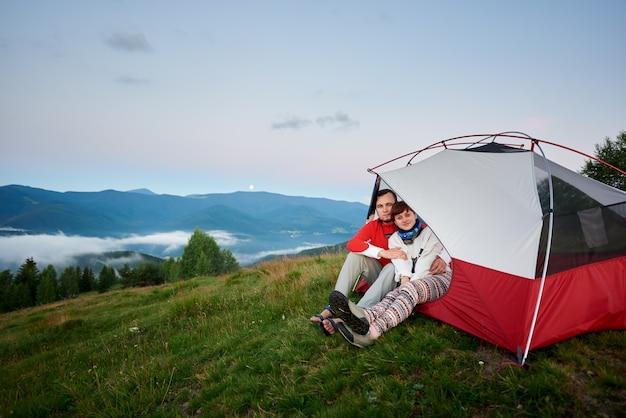Пара обниматься сидеть в палатке