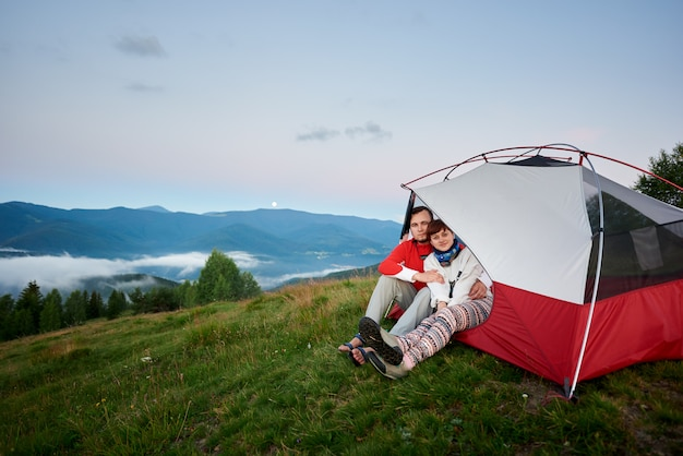Couple hugging sit in a tent