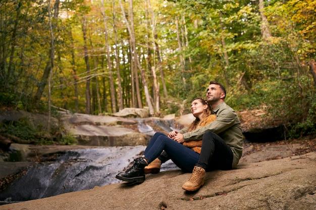 Пара обниматься, сидя у реки в лесу