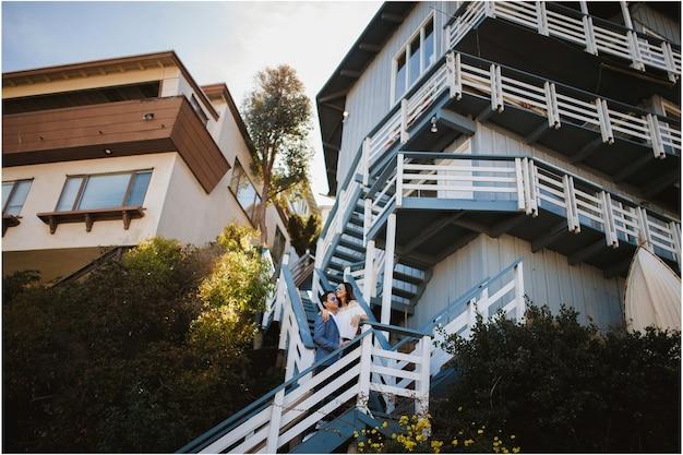 Couple hugging on the staircase, indian brunette guy hug  asian girl in white clothing.