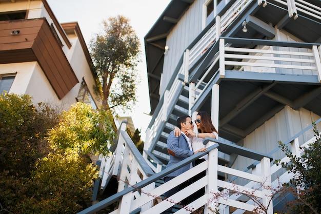 Couple hugging on the staircase, indian brunette guy hug  asian girl.