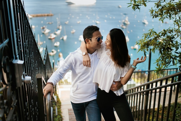 Couple hugging on the staircase with ocean view, indian brunette guy hug  asian girl.