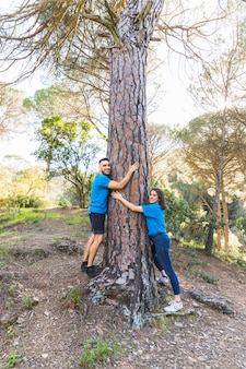 Couple hugging tree in beautiful forest