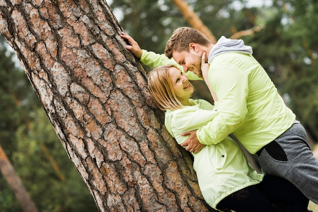 Couple hugging next to a tree