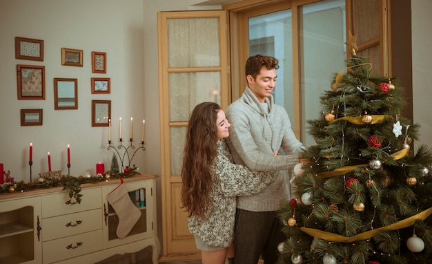 Couple hugging while decorating home for christmas