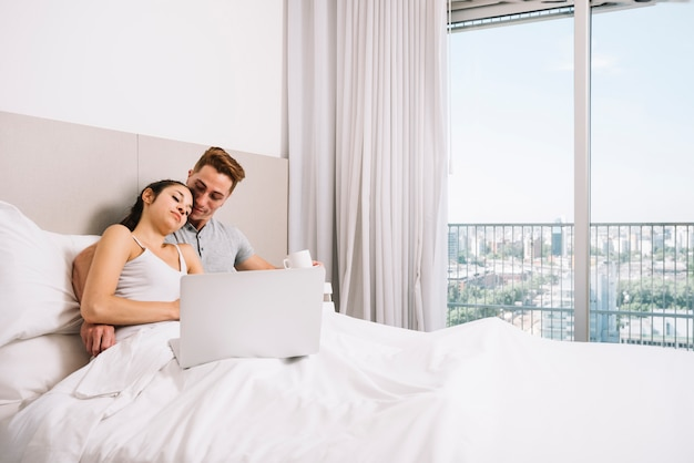 Couple hugging in white bed with laptop