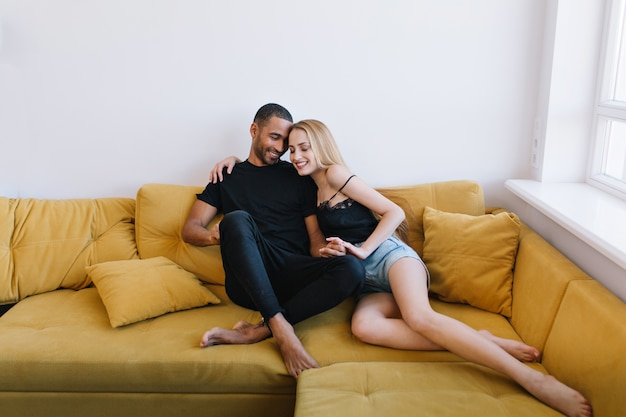 Couple hugging with eyes closed on the couch. lovers holding hands, hugging. happy faces, warm relationship, love, romance.