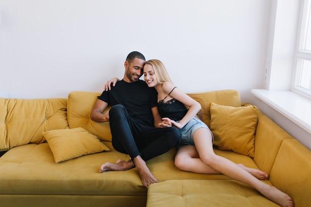 ソファで目を閉じて抱き締めるカップル。手をつないで、ハグ愛好家。幸せそうな顔、温かい関係、愛、ロマンス。