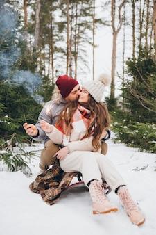 한 쌍은 썰매에 앉아 있는 동안 겨울 침엽수림에서 폭죽을 껴안고 태운다