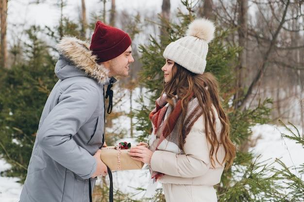 겨울 침엽수 숲에서 커플 포옹과 키스, 선물 상자를 서로 주고