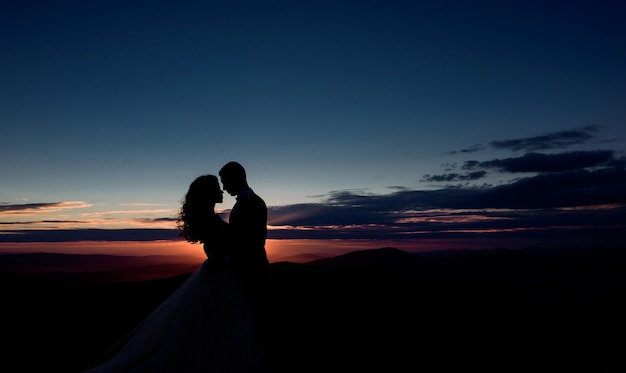 Couple hugs before violet evening sky over the mountains