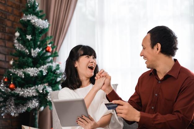 커플은 온라인 시장에서 크리스마스 판매 거래를 사냥합니다. 신용 카드 결제를 이용한 현대적인 쇼핑