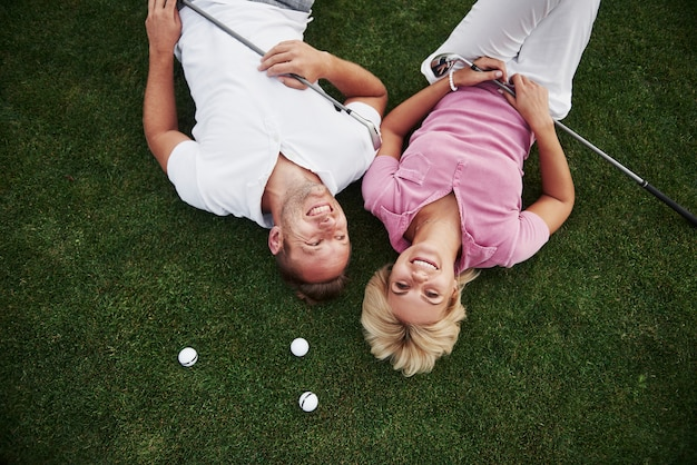 A couple, husband and wife lie on the golf course and relax after the game