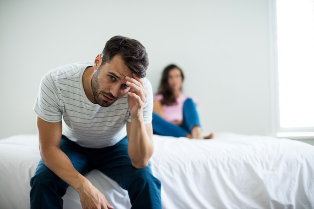 Couple ignoring each other in bedroom at home
