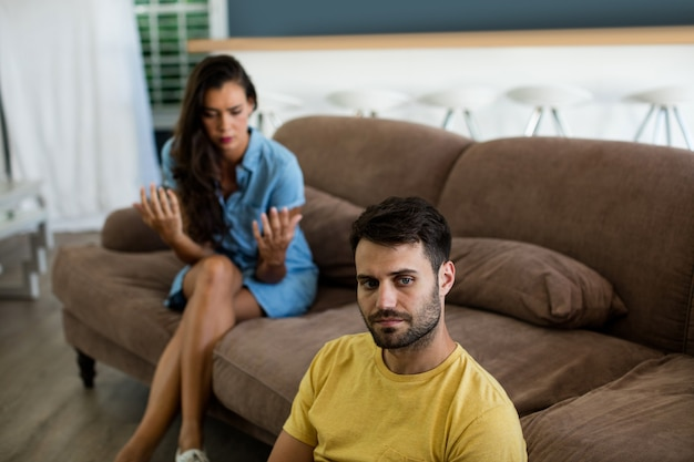 Couple ignoring each other in living room at home