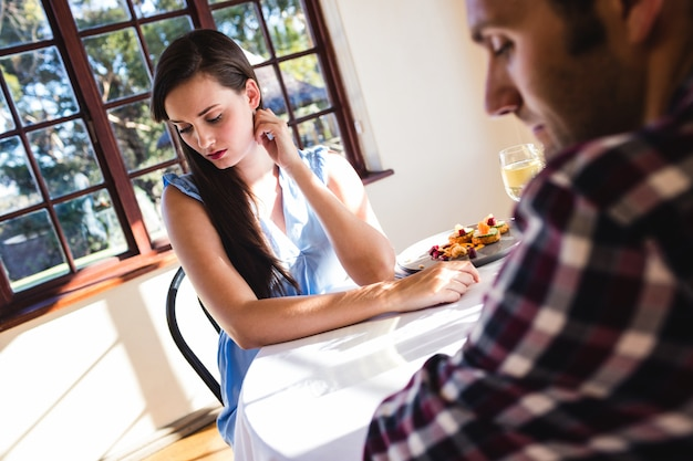 Couple ignoring each other in restaurant