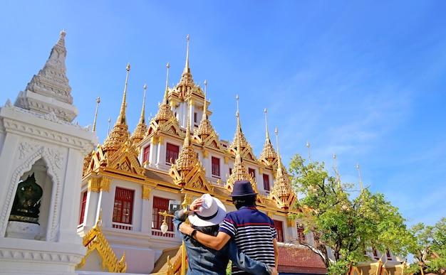 Couple impressed by the amazing loha prasat iron castle inside wat ratchanatdaram temple, bangkok old city, thailand
