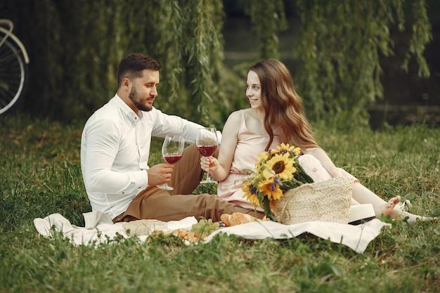 フィールドのカップル。白いドレスを着たブルネット。草の上に座っているペア。