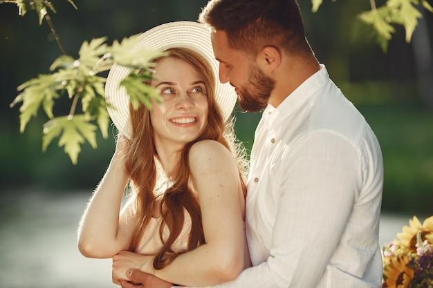 フィールドのカップル。白いtシャツのブルネット。草の上に座っているペア。