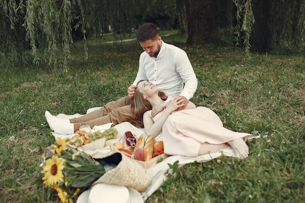 Пара в поле. брюнетка в белой футболке. пара сидит на траве.