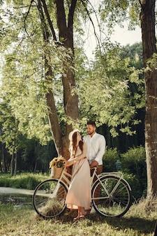 Пара в летнем парке. люди со старинным велосипедом. девушка в шляпе.