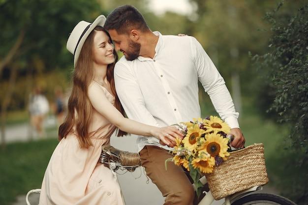 夏の公園のカップル。ビンテージ自転車を持つ人々。帽子の少女。