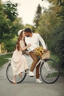 여름 공원에서 커플. 빈티지 자전거를 가진 사람들. 모자에있는 여자.