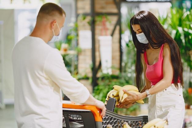 スーパーマーケットのカップル。医療マスクの女性。人々はparchasesを作ります。